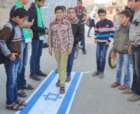 »Al-Kutla-al-Islamiya«, die für Schüler und Studenten zuständige »Bildungsabteilung« der Hamas, feiert in der UNRWA-geführten Yabna-Mittelschule in Rafah einen »Sieg« über Israel, indem sie Schüler unter anderem auf der israelischen Fahne herumtrampeln lässt. Rafah, 1. Dezember 2013