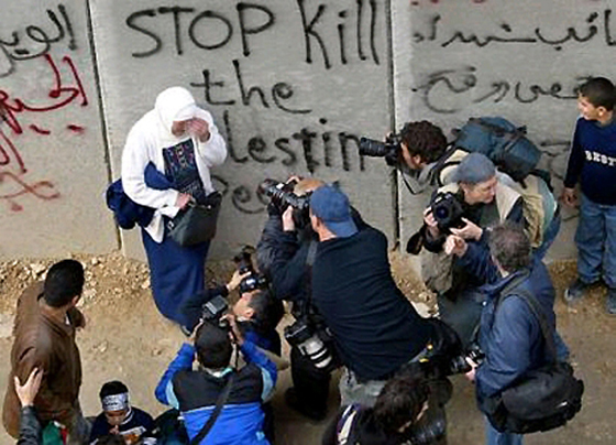 Westliche Fotografen machen an der Sicherheitsmauer, die von Israel zum Schutz vor Terroristen gebaut wurde (der deutlich überwiegende Teil der Trennanlage besteht aus einem Zaun), Aufnahmen von einer palästinensischen Frau, die zuvor gebeten wurde, sich weinend vor den englischen Schriftzug zu stellen (etwa Frühjahr 2006)
