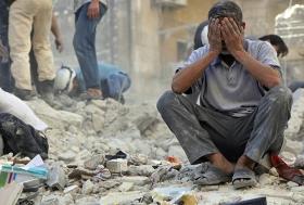 Ein Mann sitzt nach einem Luftangriff von Assads Truppen in den Trümmern seines Hauses. Aleppo, April 2014.